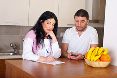 Sad couple calculate their bills. And having conversation in kitchen Royalty Free Stock Photos