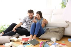 Sad couple calling to police after home robbery. Sad couple calling to police sitting on the floor of the messy living room after home robbery Royalty Free Stock Image