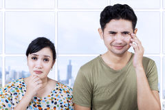 Sad couple expression in apartment Stock Image