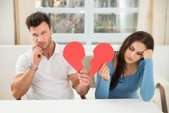 Sad couple holding broken heart Stock Photos