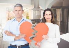 Sad couple holding broken hearts at home Royalty Free Stock Photos
