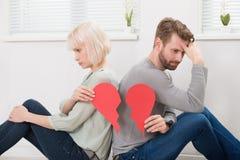 Sad Couple Holding Red Broken Heart Stock Image