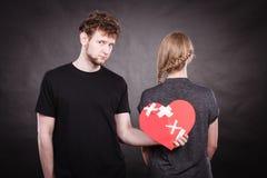 Sad couple holds broken heart. Royalty Free Stock Photography