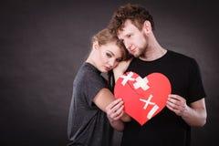 Sad couple holds broken heart. Stock Image