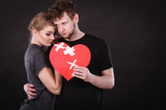 Sad couple holds broken heart. Broken heart difficult love concept. Sad unhappy couple women and men holding paper red heart fixed with plaster bandage. Rift in Stock Photography