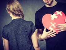 Sad couple holds broken heart. Royalty Free Stock Photos