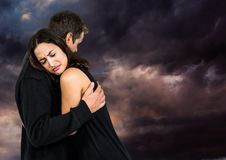 Sad couple hugging against dark cloudy sky Stock Photography