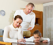 Sad couple with kids. Poor family counting money to pay bills at home. Focus on woman stock photography