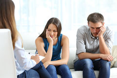 Sad couple listening to a marriage counselor. During a therapy sitting on a sofa at home Stock Image