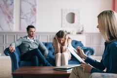 Sad couple listening to psychologist during a therapy sitting on a sofa at home. stock photos