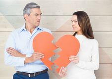 Sad couple looking each other while holding broken hearts Royalty Free Stock Photography