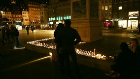 Sad couple and other people looking at candles in the center of Strasbourg stock video footage