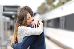 Sad couple saying goodbye before travel. Sad couple hugging saying goodbye before train travel stock photography