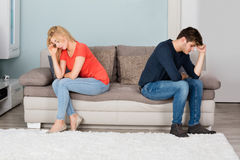 Sad Couple Sitting Back To Back On Sofa. Sad Angry Cheating Couple Sitting Back To Back On Sofa At Home Royalty Free Stock Photos