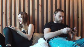 Sad couple sitting on the bed, not talking to each other, using the smartphones. Young man and woman having quarrel. stock footage