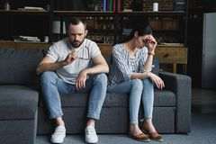 Sad couple sitting on couch at home after quarrel. And looking away stock photos