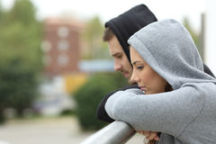 Sad couple of teens looking down in a balcony. Side view of a sad couple of teens looking down after break up in a balcony of a house with an urban background Stock Photos