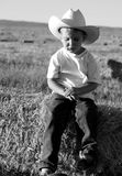 Sad cowboy. A black and white image of a sad little cowboy wearing a cowboy hat sitting on a bale of hay in a hayfield Stock Photos