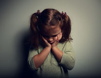 Sad crying alone kid girl on dark background. Closeup portrait Stock Photography