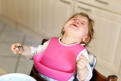 Sad crying baby girl. Toddler does not eating. Hysterical child learning eat by itself.  Royalty Free Stock Photography