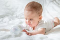 Sad and crying Infant baby girl lying on the white bed with special bottle of water with nipple. Tries to gnaw her. teething. Child childhood caucasian cute royalty free stock image