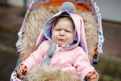 Sad crying little beautiful baby girl sitting in the pram or stroller on autumn day. Unhappy tired and exhausted child royalty free stock images