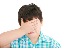 Sad crying little boy covers his face royalty free stock image