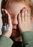 Sad crying little boy covers his face with hands Royalty Free Stock Photography