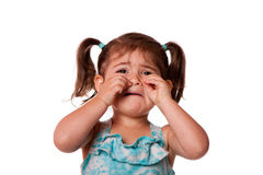 Sad crying Little toddler girl. Sad unhappy crying cute little young toddler girl wiping tears, isolated royalty free stock photography