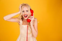 Sad crying screaming young blonde woman talking by telephone. Image of sad crying screaming young blonde woman standing isolated over yellow wall background Stock Photography
