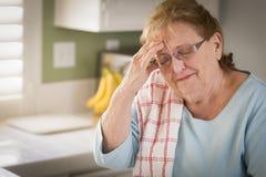 Sad Crying Senior Adult Woman At Kitchen Sink royalty free stock photos