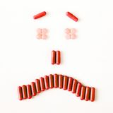 Sad and crying smile made from many pills capsules. wellness concept Stock Photos