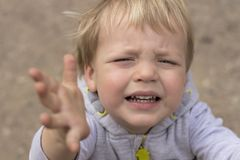 Sad crying toddler pulls his hands up. Close up portrait of baby boy asking for pick up.  royalty free stock images