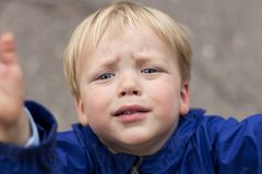 Sad crying toddler pulls his hands up. Close up portrait of baby boy asking for pick up.  stock photography