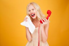 Sad crying young blonde woman talking by telephone. Royalty Free Stock Photos