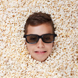 Sad crying young boy in stereo glasses looking out of popcorn Royalty Free Stock Images
