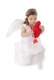 Sad cupid girl sitting with heart Stock Photo
