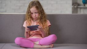 Sad curly-haired girl sitting on sofa and playing on smartphone, addiction. Stock photo stock images