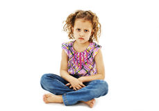 Sad curly little girl, sitting Stock Image