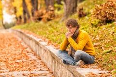 Sad curly man siting outdoor Stock Photos