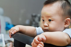 Sad cute asian baby watching out Stock Image