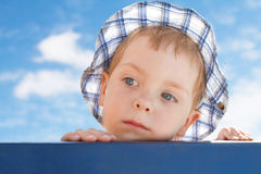 Sad cute little boy in hat on sky background Royalty Free Stock Images
