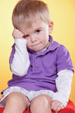 Sad cute little boy holding hand near head Royalty Free Stock Images