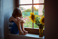 Sad cute little toddler child, sitting on a window, playing with. Sunflower on sunset royalty free stock images