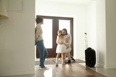 Sad daughter embracing dad leaving family saying goodbye to fath. Little kid girl embracing dad leaving family moving out with travel case, sad daughter hugging royalty free stock photos