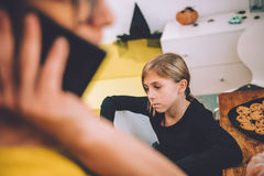 Sad Daughter listen mothers talking on smart phone Royalty Free Stock Images