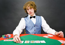 Sad dealer. A casino dealer looking sadly at the cards on the table in front of him Stock Image