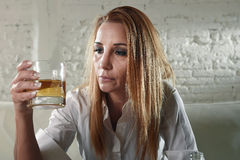 Sad depressed alcoholic drunk woman drinking at home in housewife alcohol abuse and alcoholism. Blond sad and wasted alcoholic drunk woman sitting at home sofa stock image