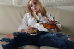 Sad depressed alcoholic drunk woman drinking at home in housewife alcohol abuse and alcoholism. Blond sad and wasted alcoholic drunk woman sitting at home sofa stock photos