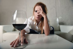 Sad depressed alcoholic drunk woman drinking at home in housewife alcohol abuse and alcoholism. Blond sad and wasted alcoholic woman sitting at home sofa couch royalty free stock photo